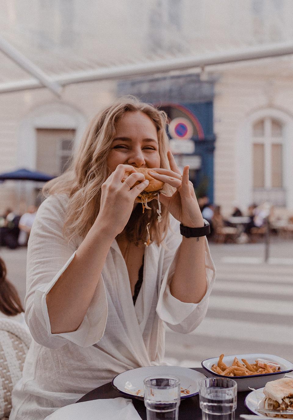 blogger Sarah Witpeerd eating a portobello mushroom burger at any burger in Paris