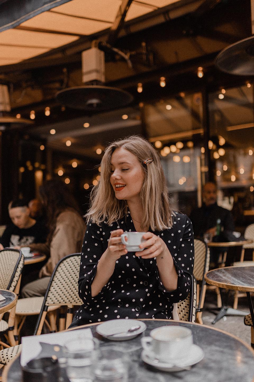 Blogger Sarah Witpeerd sitting at a Parisian cafe